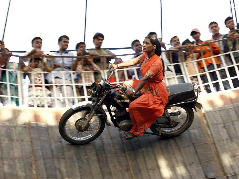 Salma Pathan performs a stunt as she rides a bike on the walls of the