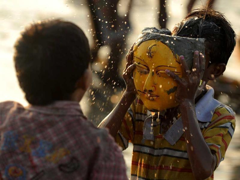 Children play with a face of Goddess Durga after the immersion of idols in the river Mahananda during the Vijaya Dashami or Dusshera Festival in Siliguri on the final day of Durga Puja.