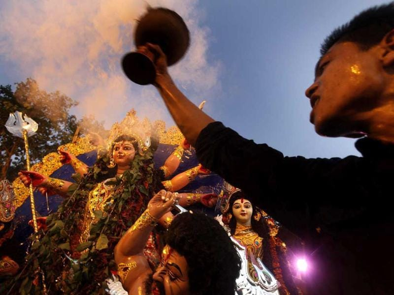 A devotee holding a pot of holy smoke dances before an idol of Hindu goddess Durga being brought for immersion in River Brahmaputra in Gauhati.