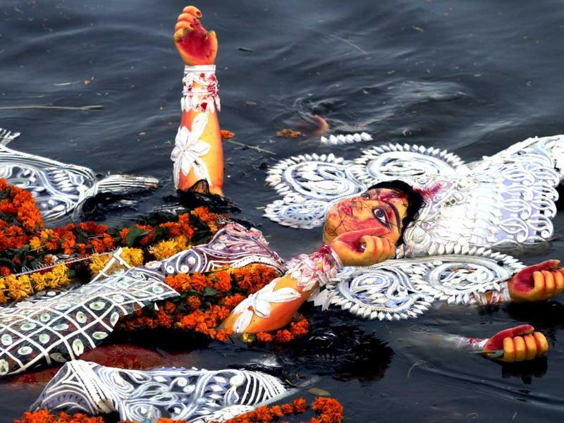 Devotees immerse an idol of Goddess Durga in river Yamuna near ISBT in New Delhi at the end of Durga puja festival.