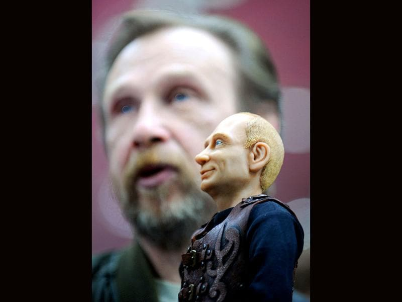 A designer Vladimir Rychkal speaks next to his doll depicting Russian Prime Minister Vladimir Putin during