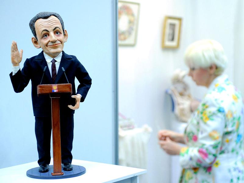 A visitor walks past a doll depicting French President Nicolas Sarkozy by designer Igor Viguzov during