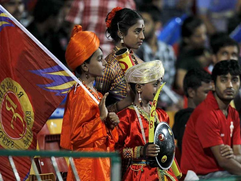 Royal Challengers Bangalore supporters sports traditional attire as the cheer for their team before the start of the Champions League Twenty20 cricket semifinal match between Royal Challengers Bangalore and New South Wales in Bangalore.