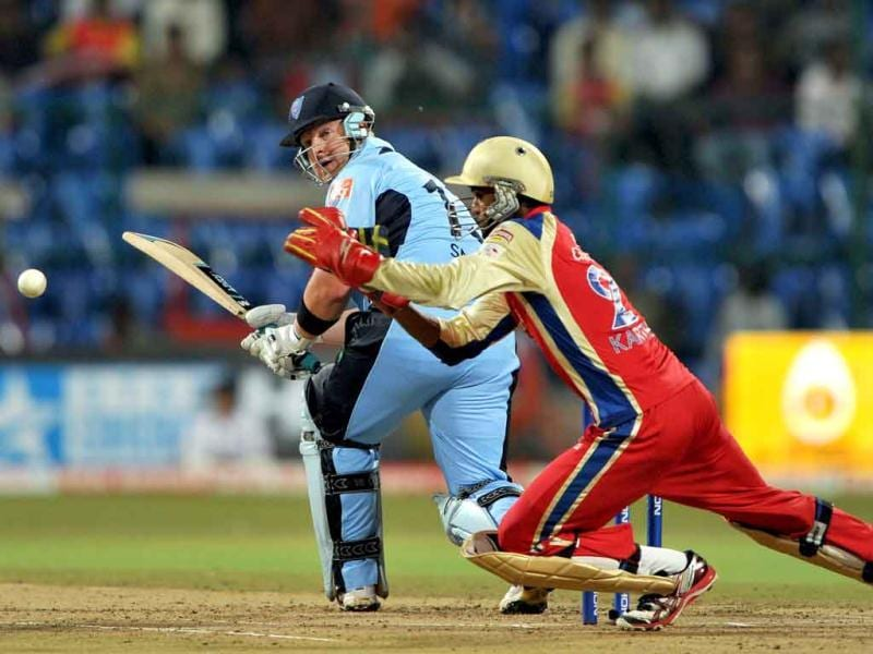RCB wicketkeeper Arun Karthik (R) is watched by NSW Blues batsman Steven Smith as he dives to stop the ball during the Champions League Twenty20 first semi final match in Bangalore.