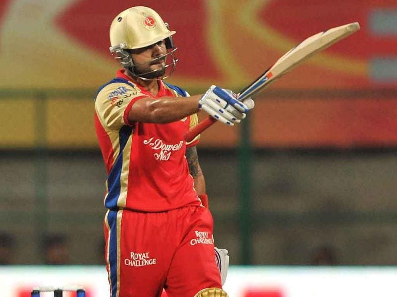 RCB batsman Virat Kholi raises his hand to acknowledge the crowd's applause after scoring 50 runs during the Champions League Twenty20 first semi final match at the M. Chinnaswamy Stadium in Bangalore.