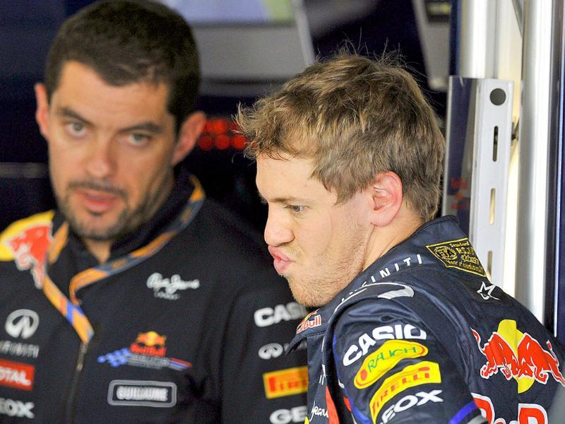 Red Bull-Renault driver Sebastian Vettel (R) of Germany talks with a team official in the pit during the third practice session of the Formula One Japanese Grand Prix at Suzuka.