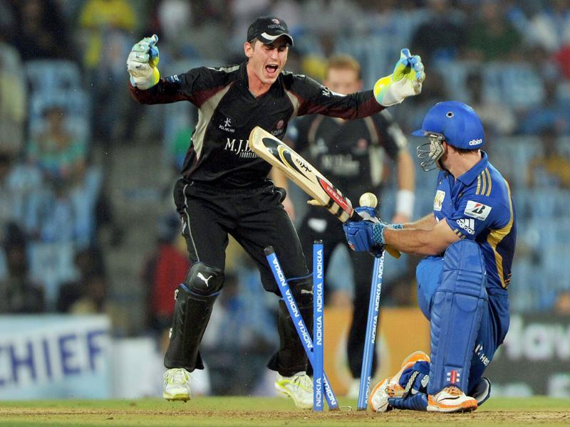 Mumbai Indians batsman Aiden Blizzard is bowled by Somerset's Murali Karthik as wicket keeper Craig Keiswetter celebrates during the Champions League Twenty20 cricket semi final match in Chennai.