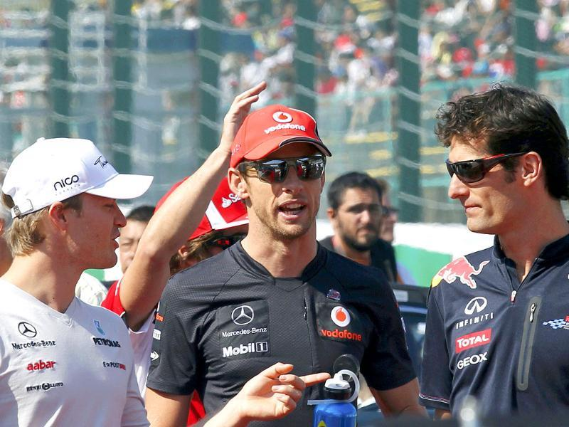 Mercedes Formula One driver Nico Rosberg of Germany (L), McLaren Formula One driver Jenson Button of Britain (C) and Red Bull Formula One driver Mark Webber of Australia talk before the drivers parade ahead of the Japanese F1 Grand Prix at the Suzuka circuit.