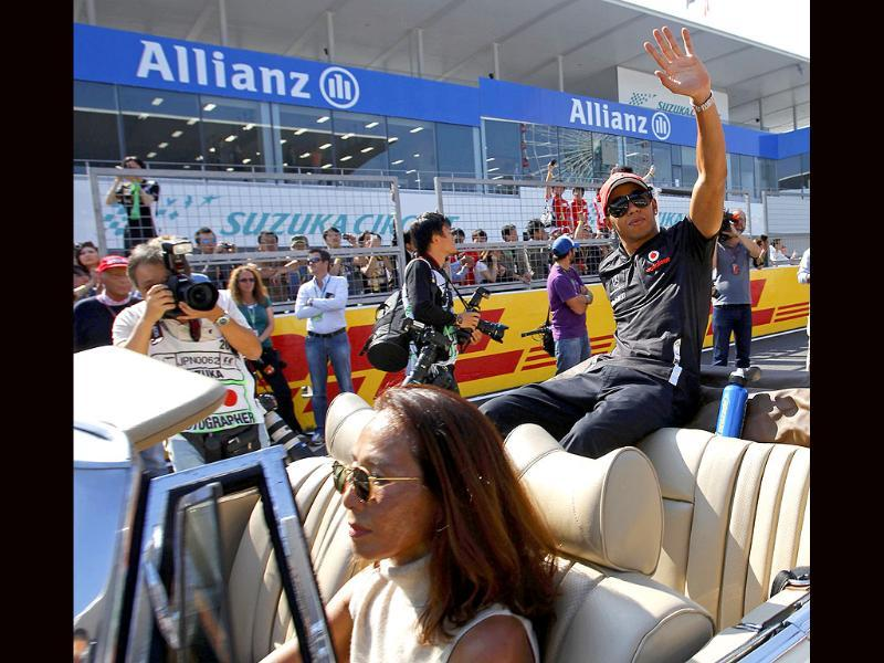 McLaren Formula One driver Lewis Hamilton of Britain (R) waves from a car during the drivers parade ahead of the Japanese F1 Grand Prix at the Suzuka circuit.