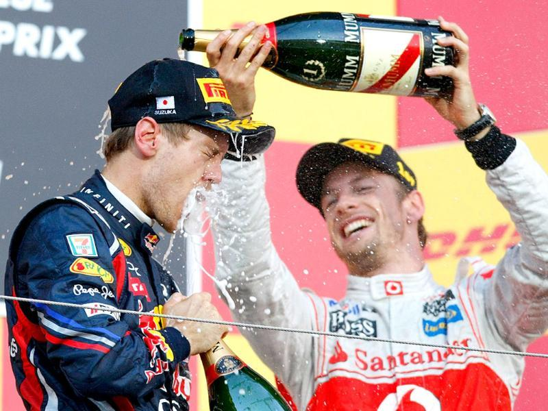 McLaren Formula One driver Jenson Button of Britain (R) pours champagne over Red Bull Formula One driver Sebastian Vettel of Germany after the Japanese F1 Grand Prix at the Suzuka circuit.