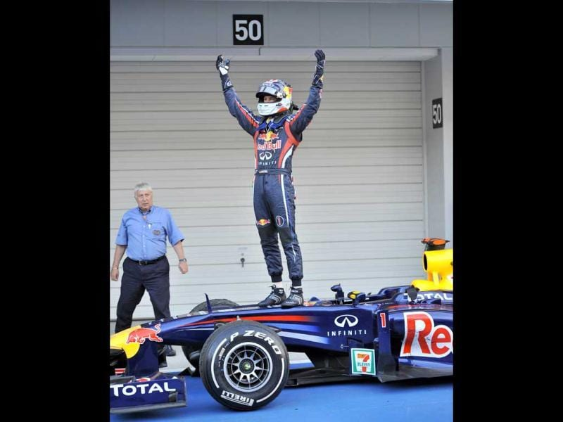 Red Bull-Renault driver Sebastian Vettel of Germany celebrates on the top of his car after finishing third and clinching the world championship at the Formula One Japanese Grand Prix at Suzuka.