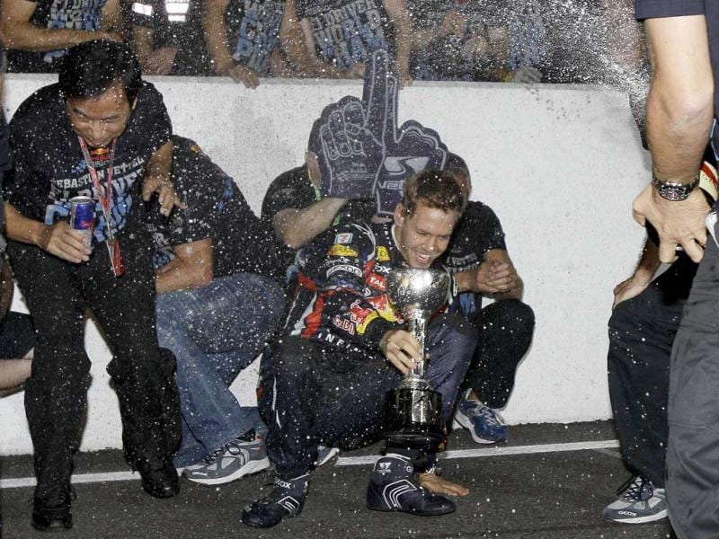 Red Bull driver Sebastian Vettel of Germany, center, gets caught in a shower of champagne while celebrates with team members after taking third place in the Japanese Grand Prix, to win the Formula One World Championship, at the Suzuka Circuit in Suzuka, central Japan.