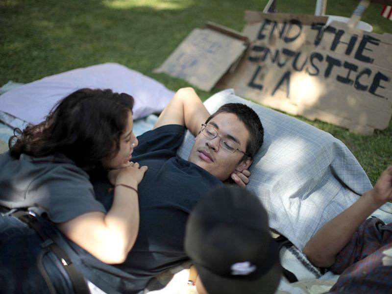 Iman Issa (L), 19 and Victor Valdez, 20, rest at the Occupy LA protest camp in Los Angeles, California. The Occupy Wall Street movement that began in New York last month with a few people has expanded to protests across the country with marches and camps taking shape from Tampa, Florida to Portland, Oregon, and Los Angeles to Philadelphia.