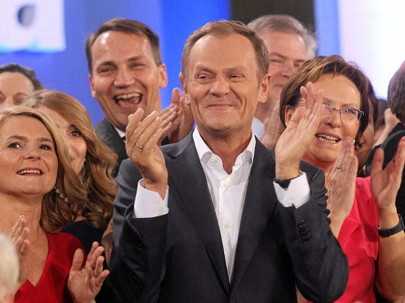 Poland's Prime Minister Donald Tusk (C), claps his hands after the election results announcement in Warsaw. Tusk claimed victory in Sunday's election after exit polls showed his ruling centre-right Civic Platform party (PO) nearly 10 points ahead of his nearest rival.