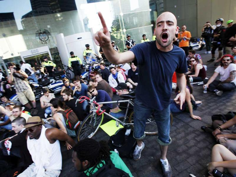 Matthew Gember, of Chicago, gestures as Occupy Boston demonstrators protest on the plaza in front of the Federal Reserve Bank in Boston.