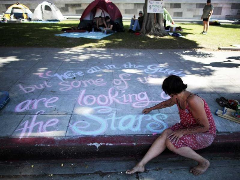 Usan Cameron, 49, writes messages in chalk on the sidewalk at the Occupy LA protest camp in Los Angeles, California.