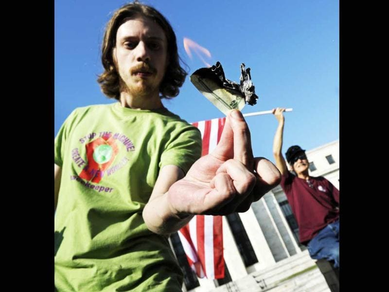Collin Rosenmarkle burns a $20 bill as protestors, who are calling for an end to the Federal Reserve and are part of the Occupy DC movement, demonstrate in front of the Federal Reserve, in Washington.
