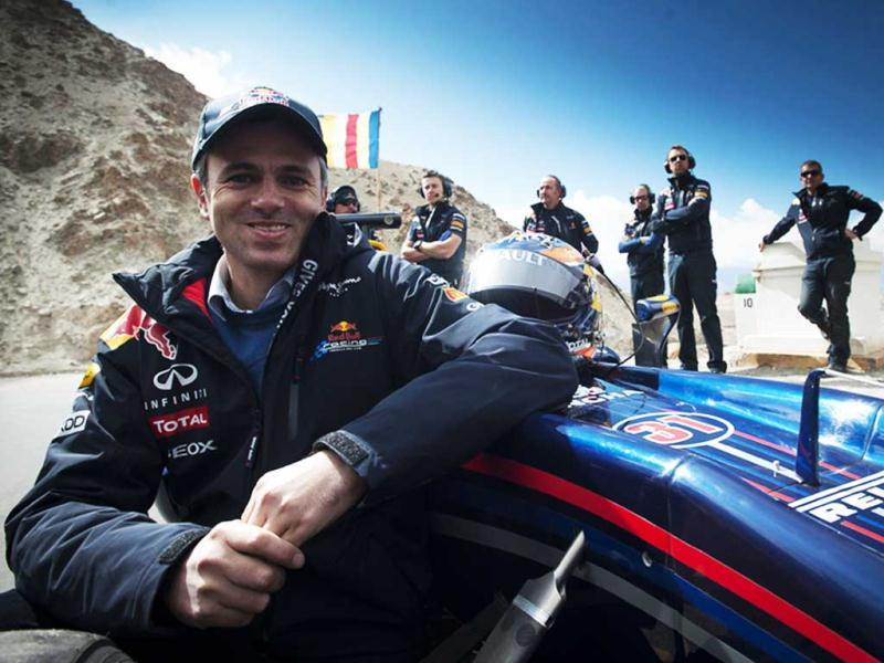 In this handout photo released on October 11, 2011, chief minister of Jammu and Kashmir Omar Abdullah poses besides a Red Bull Racing Formula One show car on the world's highest motorable road at 18,380 feet with support team members cheering him on at the Khardung-La pass in Leh region.
