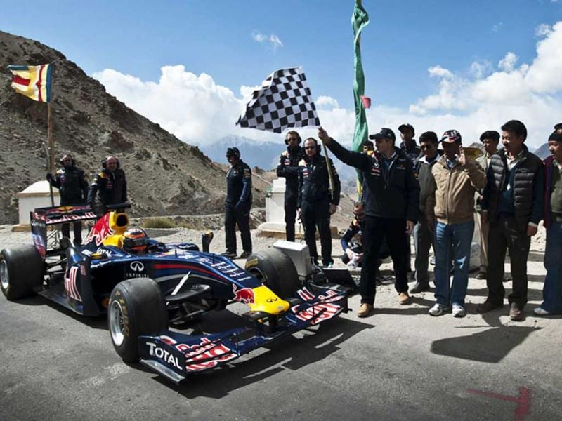 In this handout photo released on October 11, 2011, J&K CM Omar Abdullah (4R) waves a chequered flag as Red Bull racing driver Neel Jani drives a Red Bull Racing Formula One show car on the world's highest motorable road at 18,380 feet with support team members cheering him on at the Khardung-La pass in Leh region.