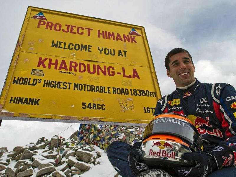 In this handout photo released on October 11, 2011, Red Bull Racing driver Neel Jani poses on the Red Bull Racing Formula One show car after driving on the world's highest motorable road at 18,380 feet on the Khardung-La pass in Leh.