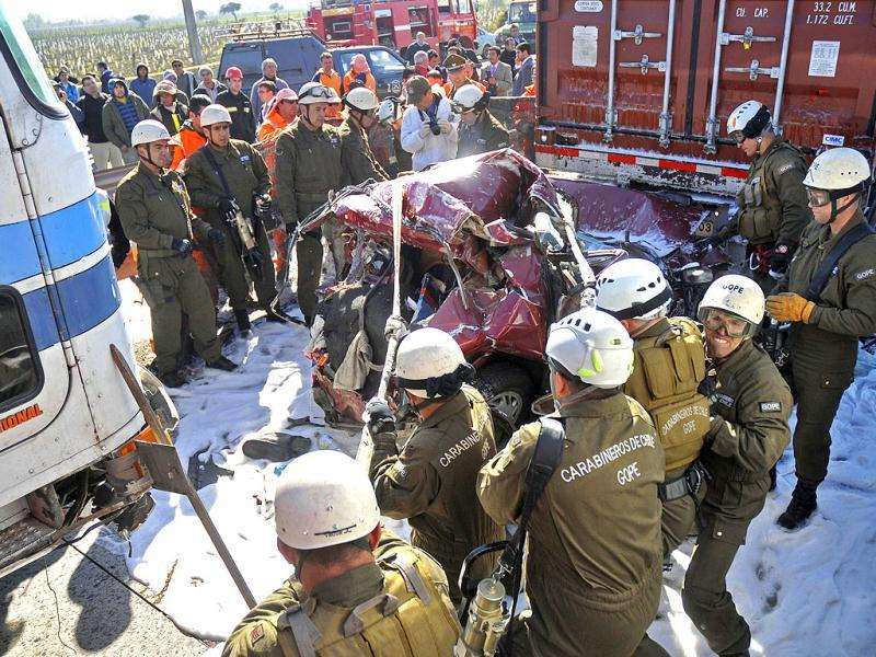 Police officers work to dislodge a car that rammed into the back of a semi-trailer in a multi-vehicle accident on a highway in Casablanca, about 43 miles or 70 kilometers from Santiago, Chile.