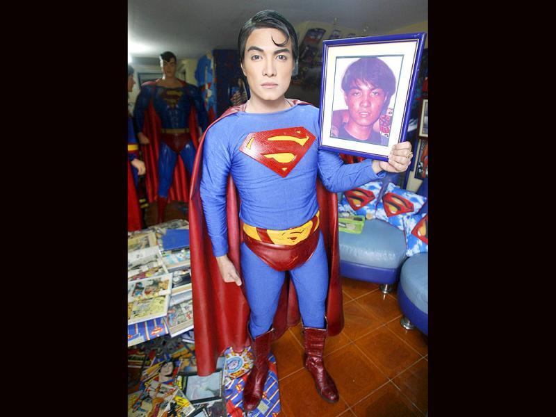 Herbert Chavez holds a photo of himself at 16, taken before his cosmetic transformation to look like his idol Superman, inside his house in Calamba Laguna, south of Manila.