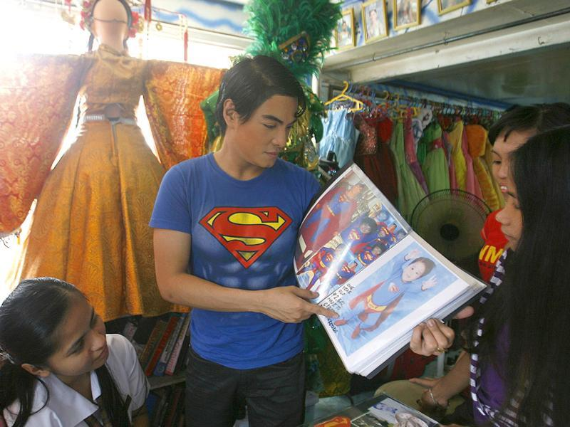 Herbert Chavez shows a catalogue of Superman costumes to his costume store staff in Calamba Laguna, south of Manila.