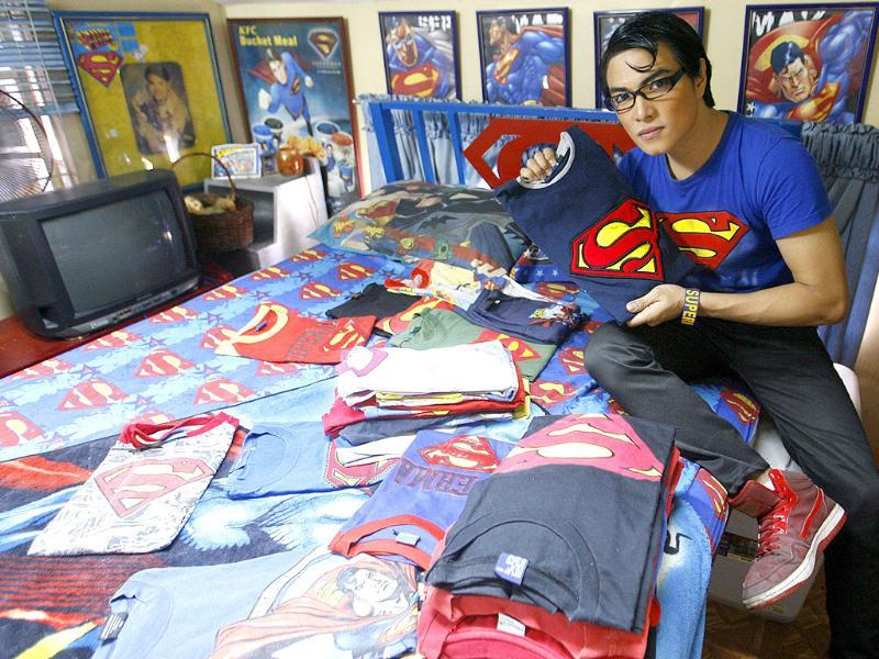 Herbert Chavez shows off his Superman shirt collection, some of which were made by him, inside his bedroom in Calamba Laguna, south of Manila.