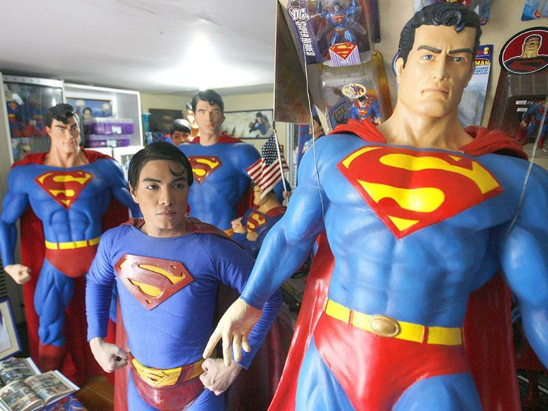 Herbert Chavez poses with his life-sized Superman statues inside his house in Calamba Laguna, south of Manila.