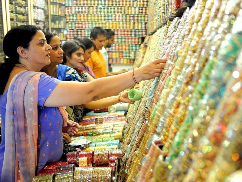 Customers inspect displays of bangles on sale in Amritsar on October 13, 2011. Bangles are in heavy demand ahead of the forthcoming Karva Chauth festival.