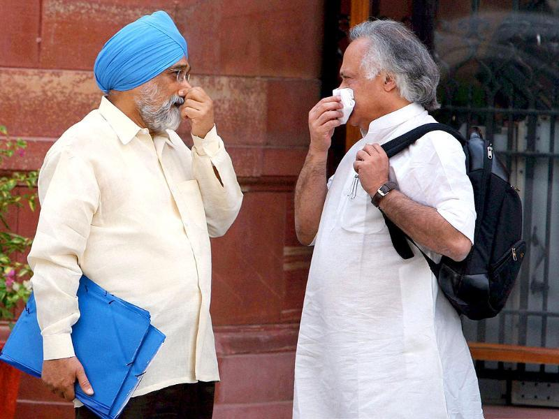 Deputy chairman of Planning Commission Montek Singh Ahluwalia and Union Rural Development minister Jairam Ramesh after a cabinet meeting in New Delhi.