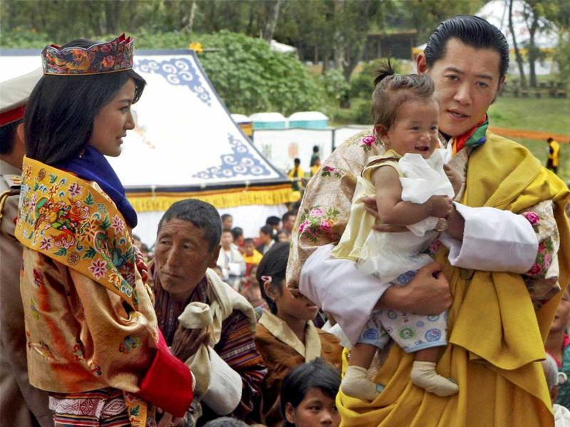 King Jigme Khesar Namgyal Wangchuck accompanied by Queen Jetsun Pema holding a baby as they meet people after their wedding at the Punakha Dzong in Punakha, Bhutan.