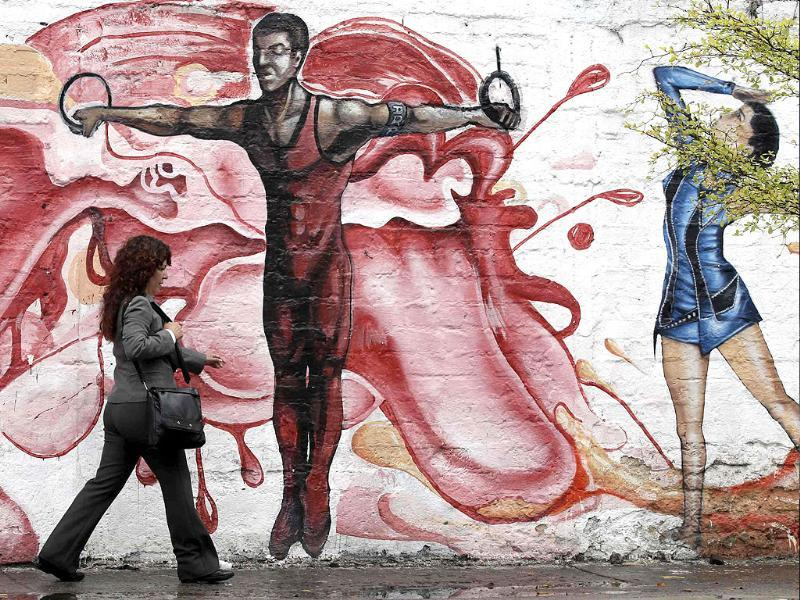 A woman walks past a mural painted to celebrate the XVI Pan American Games in Guadalajara. The games will be held from October 14 to 30.