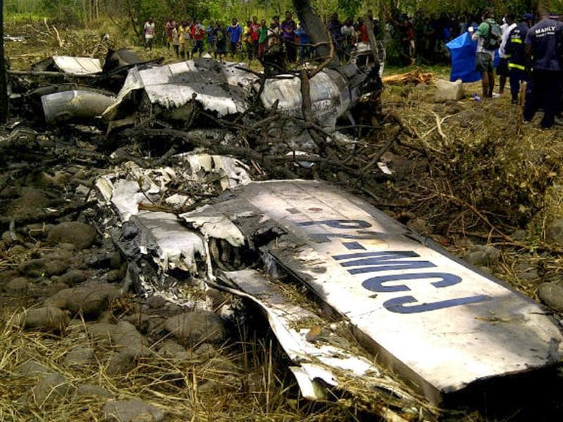 Locals gather at the crash site of an Airlines PNG Dash 8 plane near Madang in Papua New Guinea.