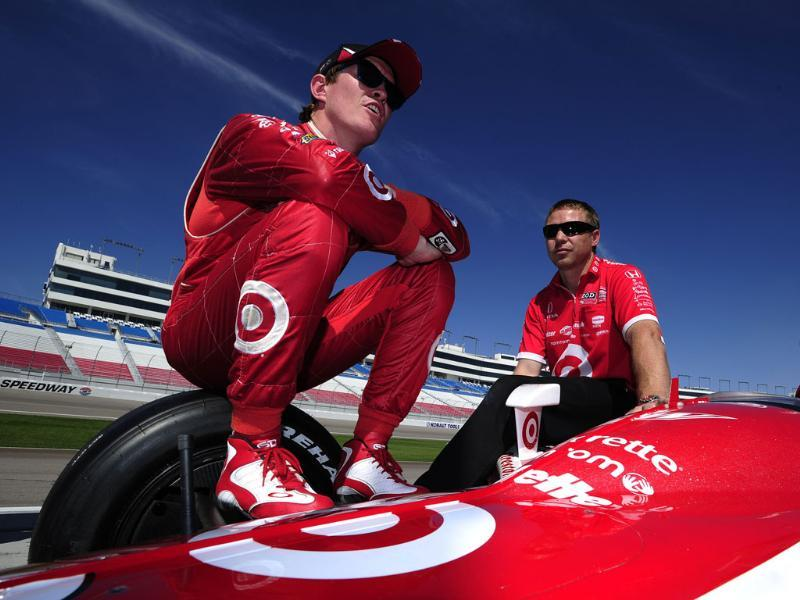 Scott Dixon of New Zealand driver of the #9 Target Chip Ganassi Racing Dallara Honda chats with team member Blair Julian also of New Zealand during practice for the IZOD IndyCar Series World Championship at the Las Vegas Motor Speedway in Las Vegas, Nevada.