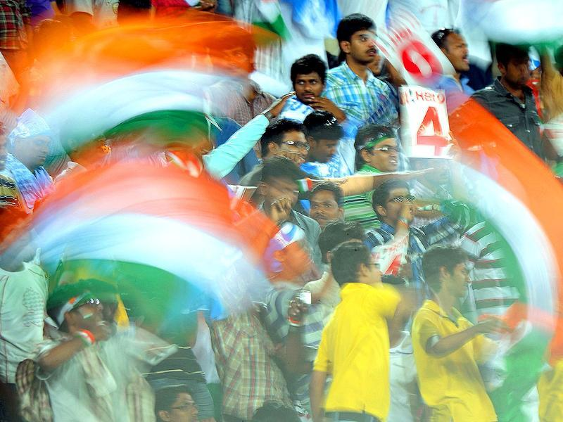 Indian cricket fans wave national flags during the first one-day international cricket match between India and England at the Rajiv Gandhi International Stadium in Hyderabad.