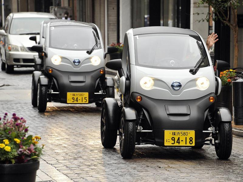 People drive Japanese auto giant Nissan's New Mobility Concept, their two-seat electric vehicle (EV), during a press preview in Yokohama city, suburan Tokyo.