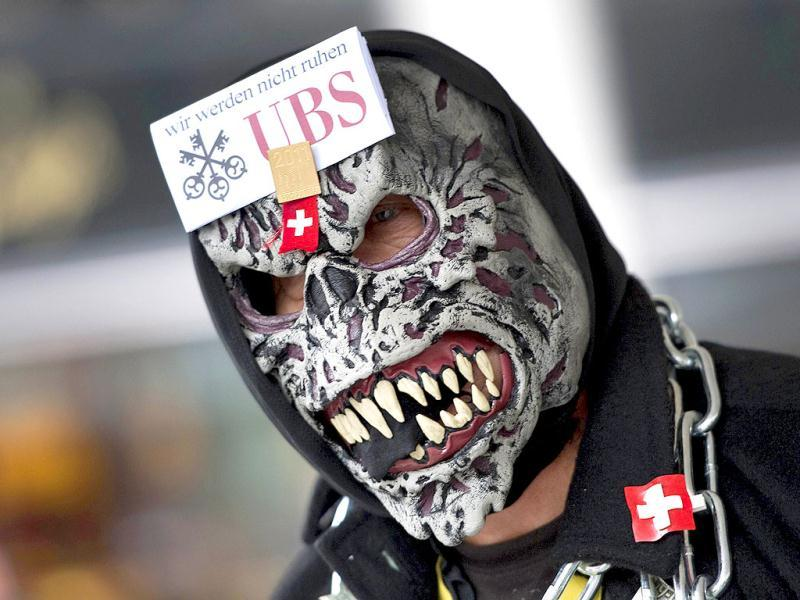 A protester wears a mask bearing the logo of the Swiss Banking giant UBS and a slogan which translates as