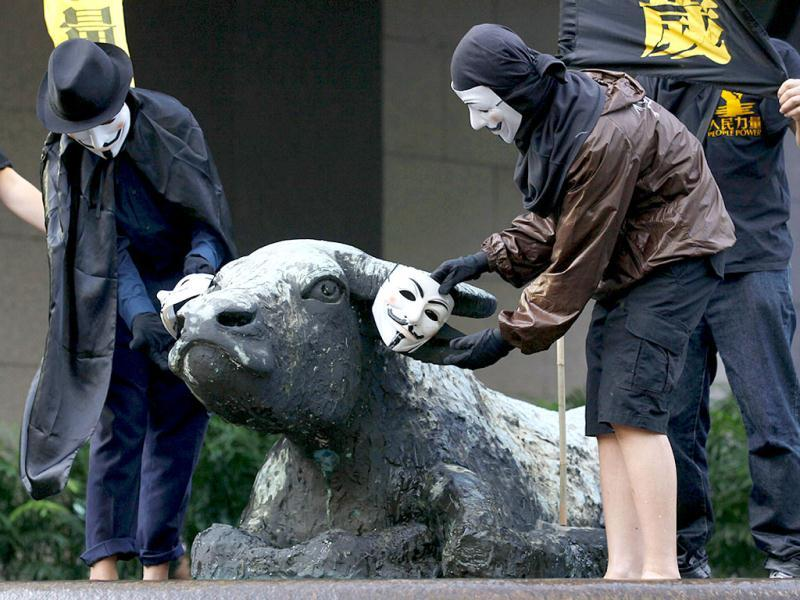Protesters place Guy Fawkes masks on the statue of bull during Occupy Hong Kong rally outside the Hong Kong Exchange Square.