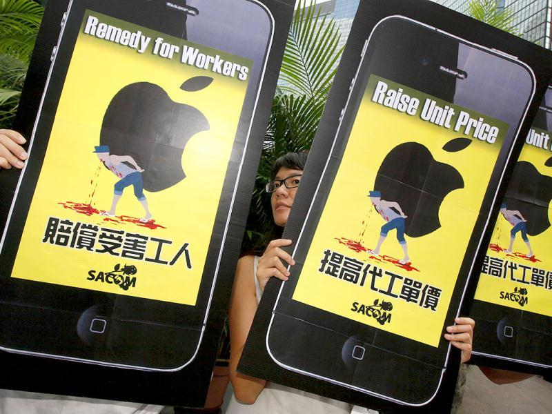 Labour activists holding cardboard cutouts resembling Apple iPhones during an Occupy Hong Kong rally outside the Hong Kong Exchange Square.