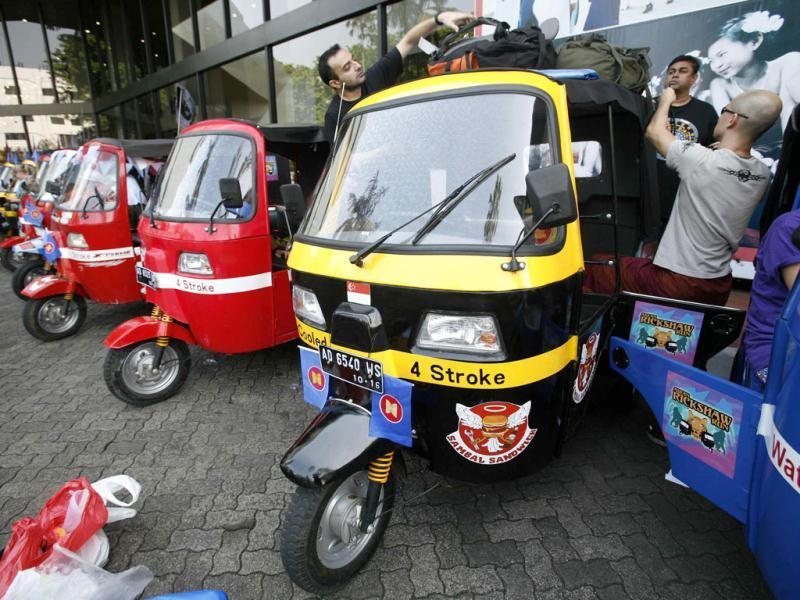Participants of the ASEAN Rickshaws Run from Singapore prepare their auto-rickshaw at the ASEAN Secretariat building in Jakarta.