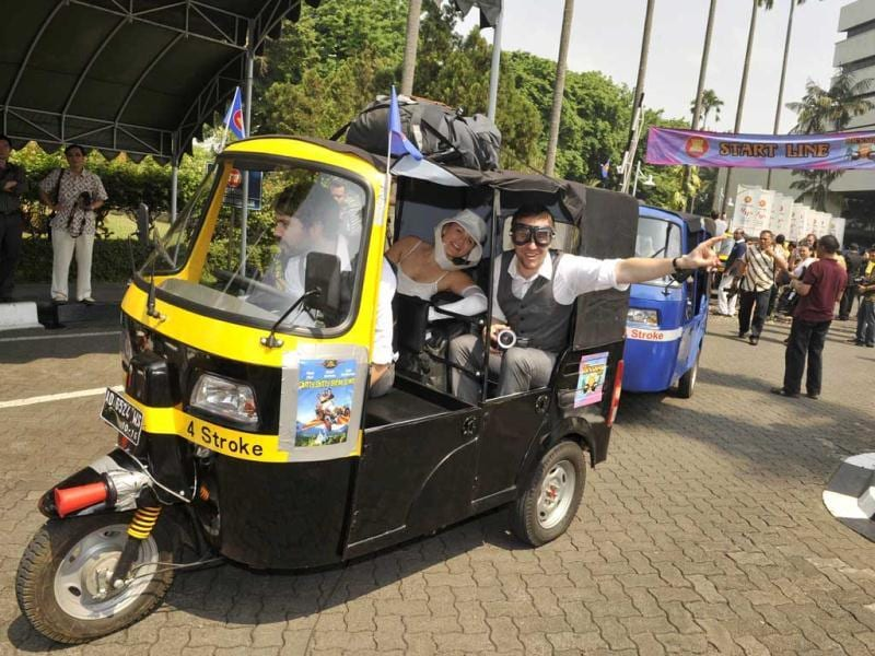 Eoin McPherson (on the wheels) from New Zealand, Kristy Ruthuen (C) and Mark Poot (R) from Australia in their auto-rickshaw start the 3,000-kilometre ASEAN Rickshaw Run in Jakarta.