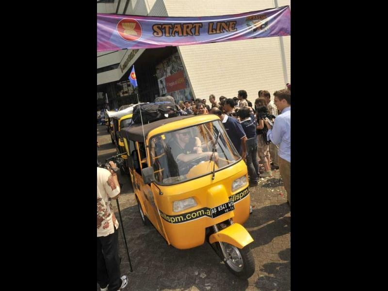 An auto-rickshaw is driven from the startline during the send-off ceremony in Jakarta.