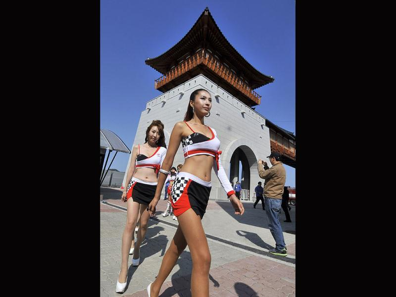 South Korean grid girls walk along the paddock as they prepare ahead of the start of the Formula One Korean Grand Prix in Yeongam.