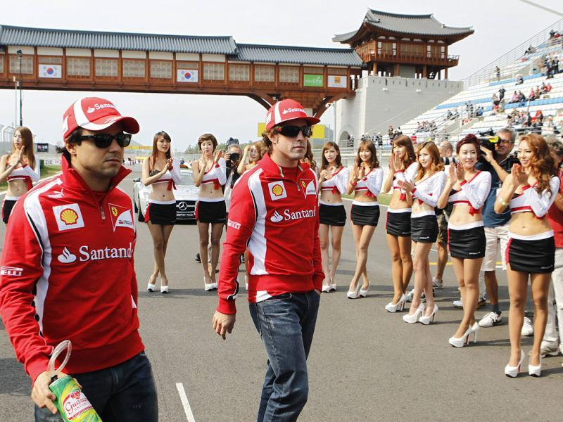 Grid girls applaud as Ferrari Formula One drivers Felipe Massa of Brazil (L) and Fernando Alonso of Spain walk out onto the grid for the drivers' parade before the South Korean F1 Grand Prix at the Korea International Circuit in Yeongam.