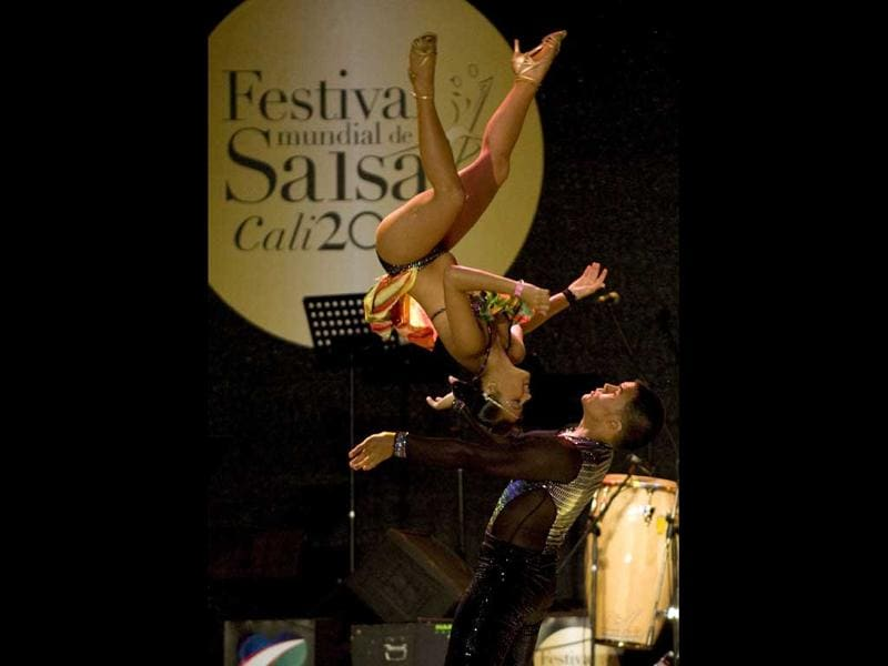 Colombian dancer Arnulfo Franco (Down) and Daniela Chavez perform during the cabaret couple category of the 6th World Salsa Festival at the Cañaveralejo Bullring, in Cali, Valle del Cauca department, Colombia.