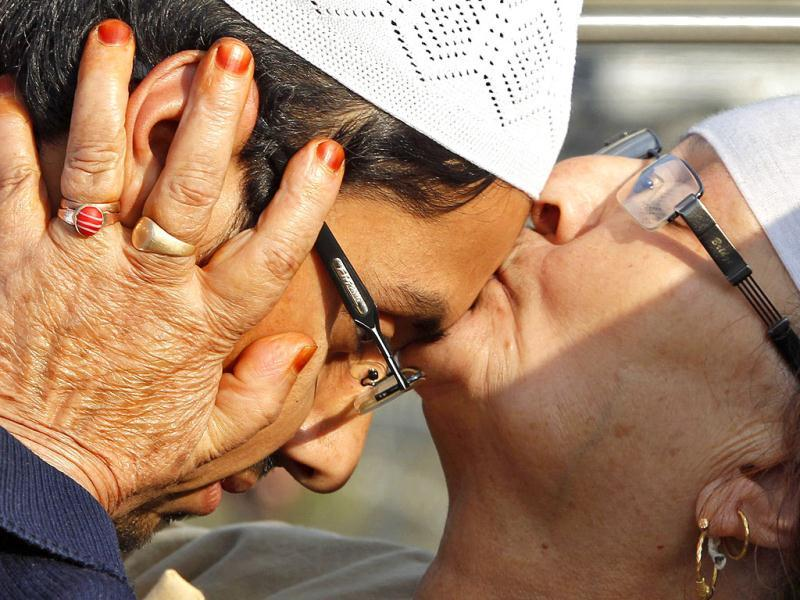 A relative kisses the face of a Kashmiri Hajj pilgrim before his departure for Mecca, in Srinagar.