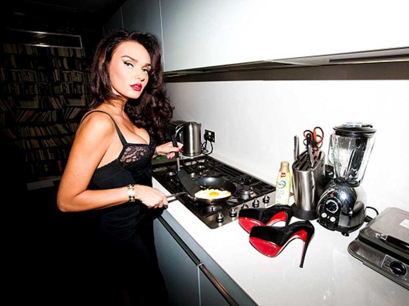 Ecclestone, clad in a black gown, can be seen cooking an egg in the kitchen. (Photo credit: www.tylershields.com)