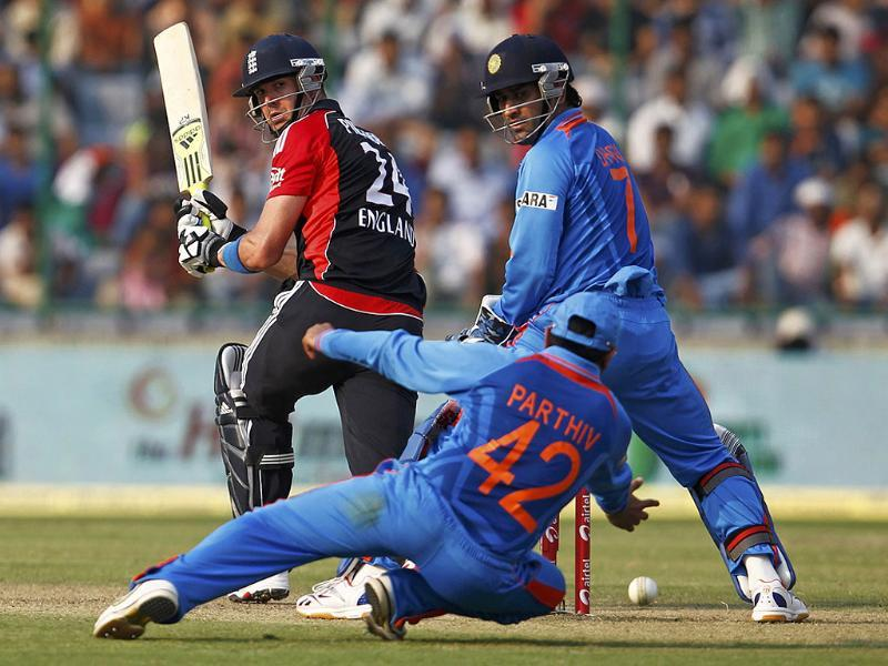 Parthiv Patel dives to field a shot hit by Kevin Pietersen as Mahendra Singh Dhoni watches during their second ODI in New Delhi.