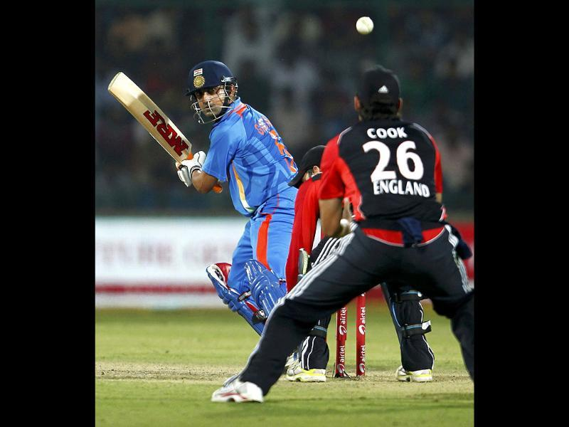 Gautam Gambhir plays a shot as England's captain Alastair Cook watches during their second one-day international cricket match in New Delhi.